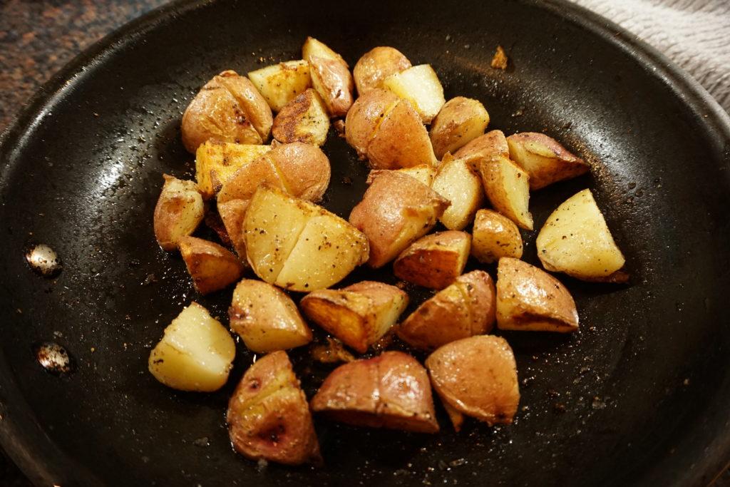 Pan fried seasoned potatoes in the works.